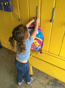 My daughter demonstrates her mastery of backpack-hook technology